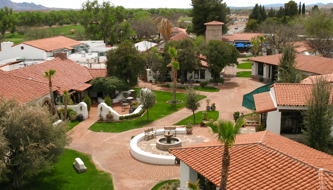 aerial view of the property with different buildings and fountain in the middle