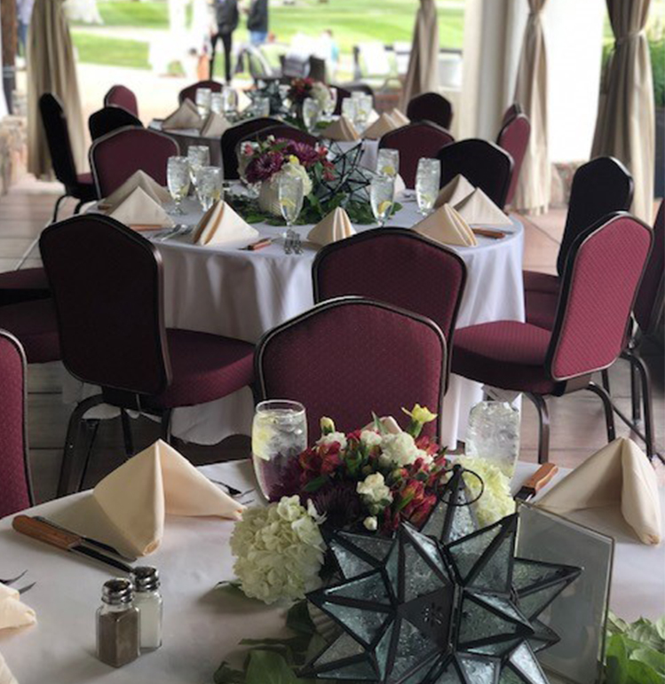event space set up with banquet tables and place settings