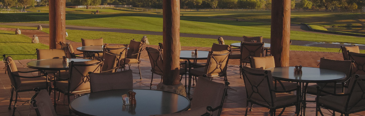 tables and chairs set up on patio outside near golf course