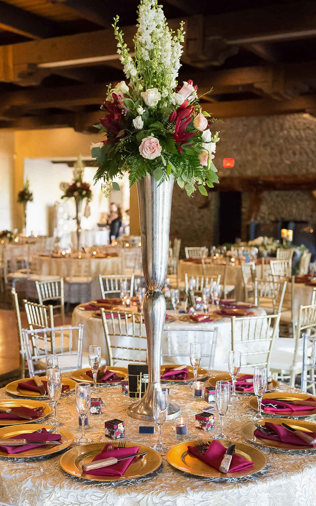 banquet style wedding table set with a tall floral centerpiece
