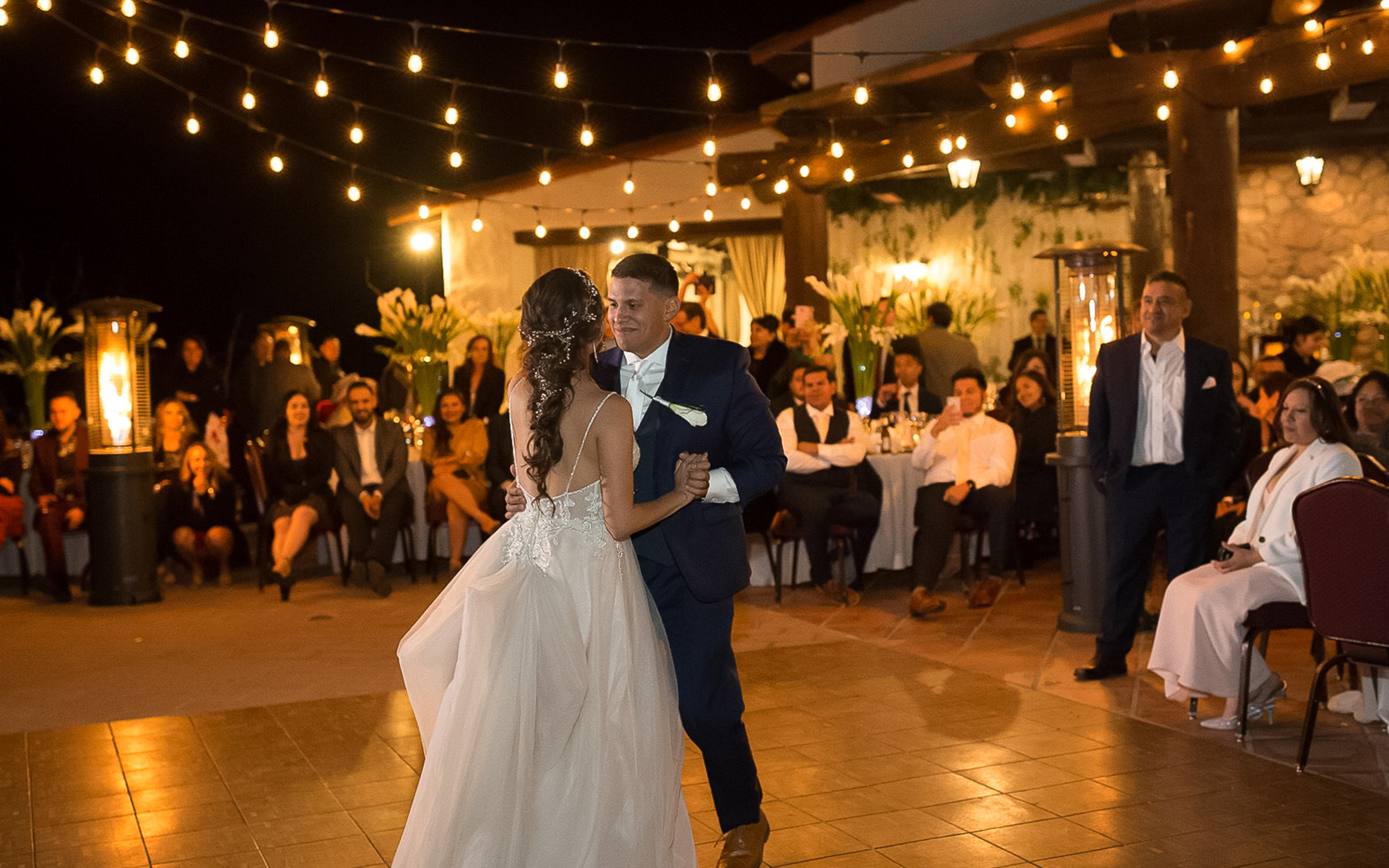 bride and groom dancing on dance floor outside with string lights