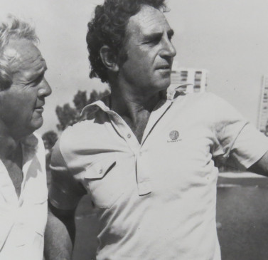 black and white image of two men on the golf course looking off to the side