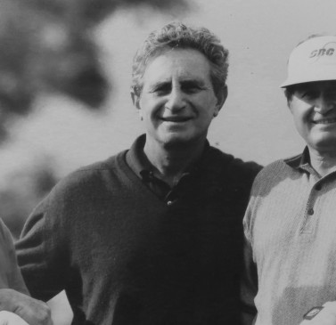 black and white image of three men wearing golf polo shirts with their arms around each other smiling at the camera