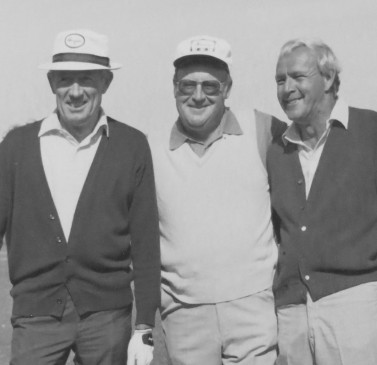 black and white image of three older men smiling while holding their golf clubs in hand on the golf course
