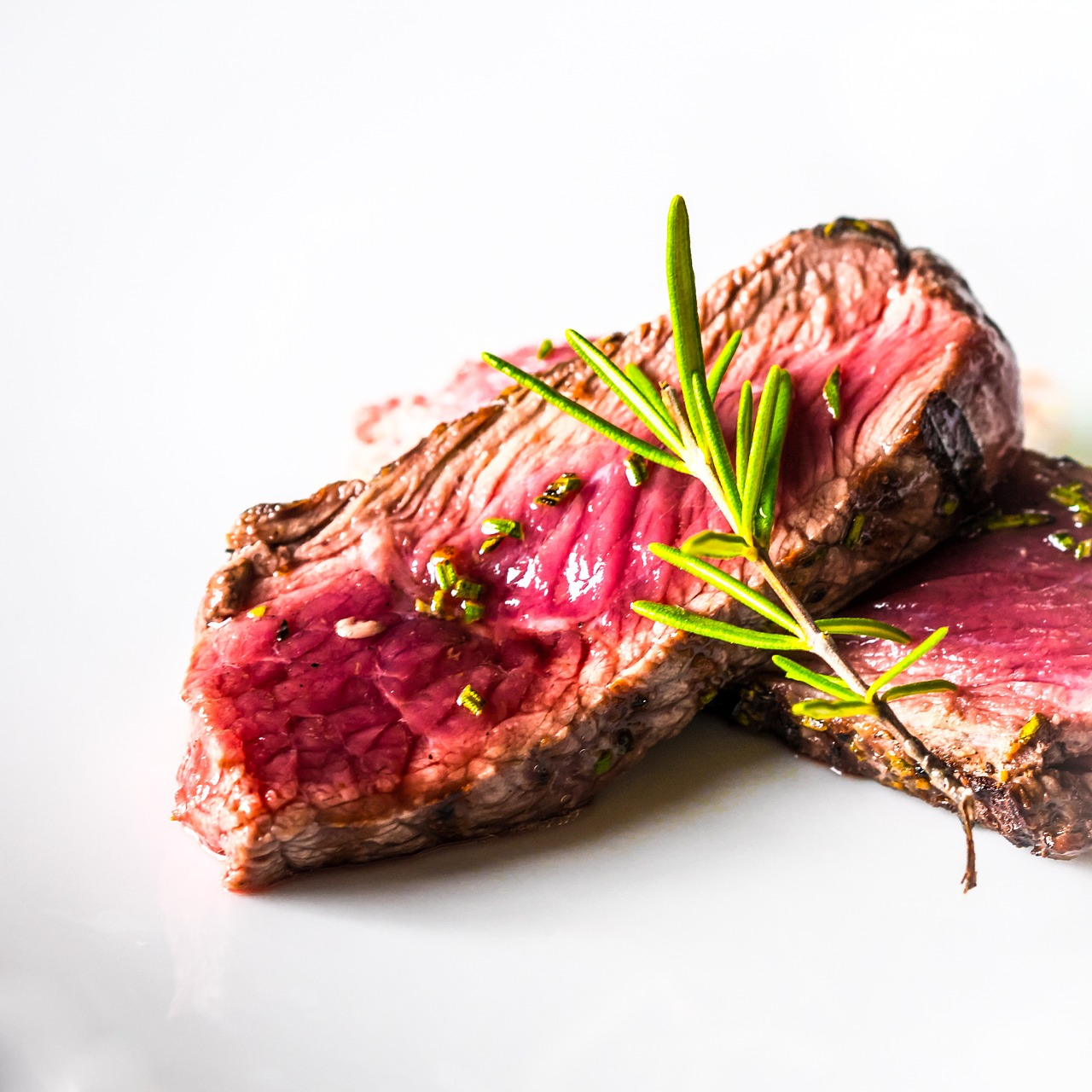 Two slices of rare cooked steak with garnish on white background