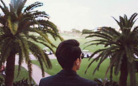 man looking out onto golf course