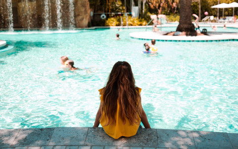 girl sitting by pool with feet in the water