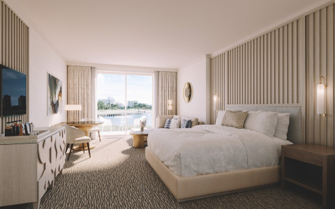 white bed in room with balcony looking over water