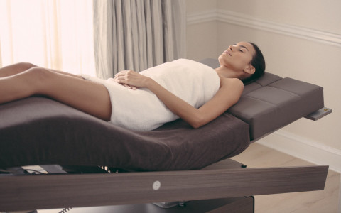 woman in towel laying on curved table at spa