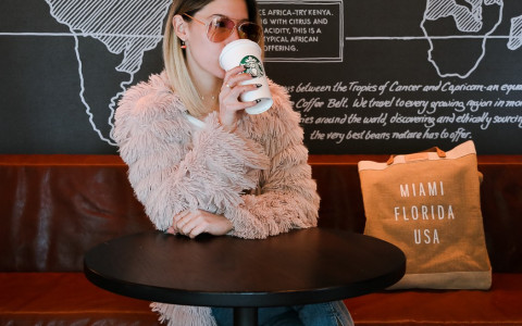 woman sitting at table drinking starbucks