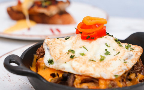 skillet dish topped with egg and peppers