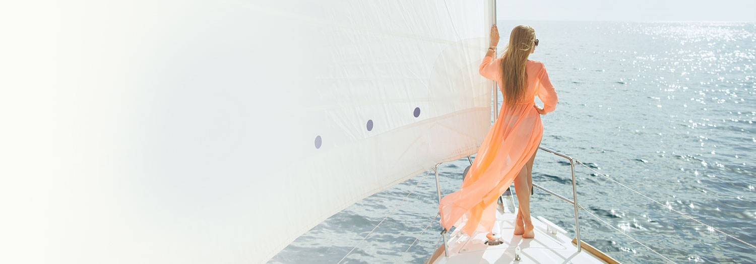 woman in long peach colored coverup standing at the front of the boat looking out at the water