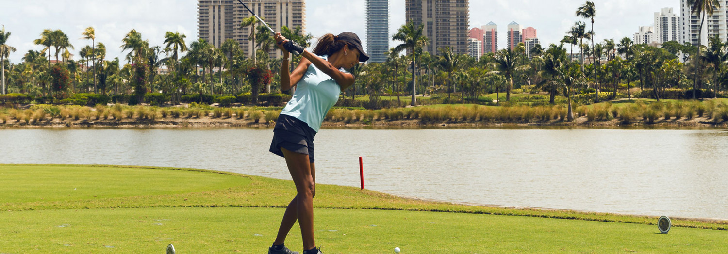 golfer swinging to hit ball with lake view