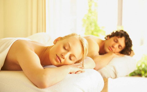 man and woman laying on separate massage tables with eyes closed