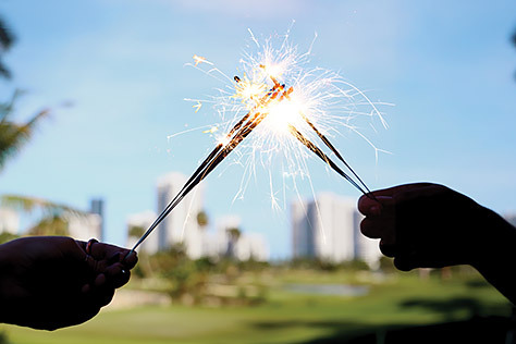 Two Hands Holding Sparklers with a golf course and skyline in the background