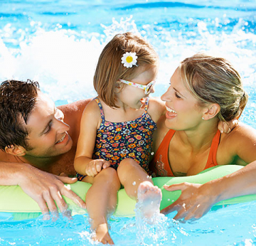 Husband, wife and little girl floating in the pool in the summer