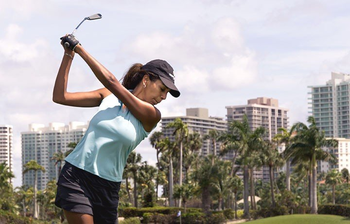 Woman swinging golf club on course