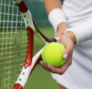 Close up of woman holding tennis ball & racket