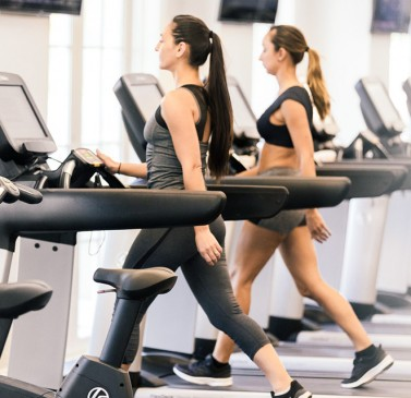 Two women walking on treadmills
