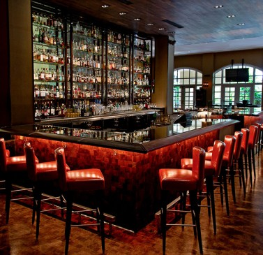 Full bar with black granite countertop & red leather stools