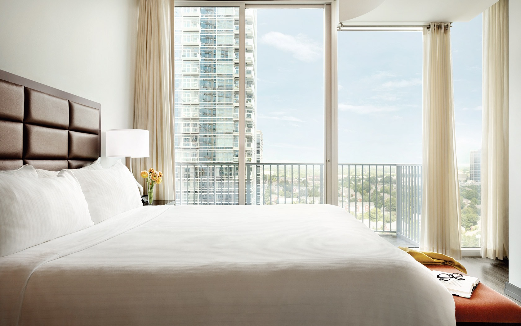 Bed with white sheets and floor length windows facing the city