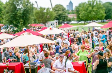 Overview of a crowd of people in the park at tables under umbrellas at the Killer Tomato Festival