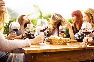 Group of friends sitting at a table drinking wine