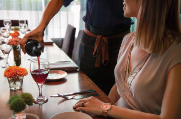 A waiter pouring a glass of wine for a woman seated at a restaurant table