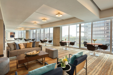A lounge area with tables, chairs, couches, and tall windows with downtown views