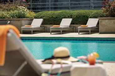 A hat sits on a cushioned lounge chair by the pool surrounded by additional lounge chairs