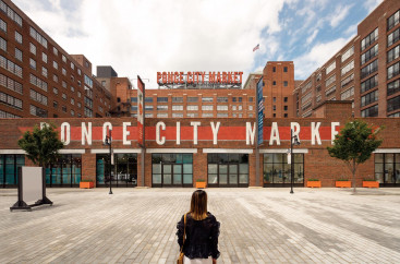 Woman sitting on gray brick ground looking at Ponce City Market sign on a building