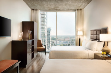 Two beds with a wooden chest and large glass window with a view of downtown