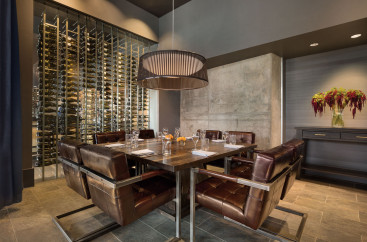 Dark wood table and leather chairs in a restaurant next to the wine cellar