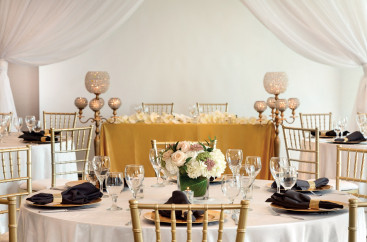 Tables set with white tablecloths and floral arrangements for an elegant event