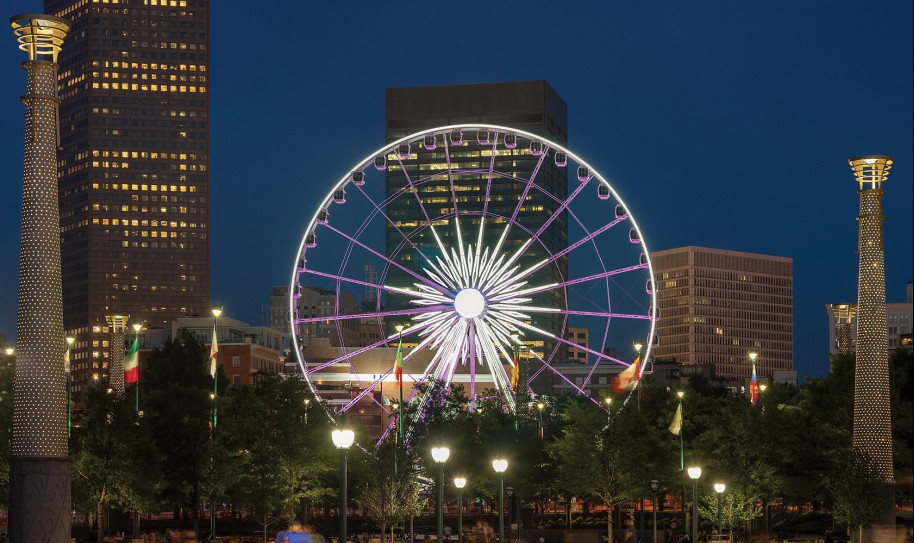 A ferris wheel lit up at night with downtown buildings in the background
