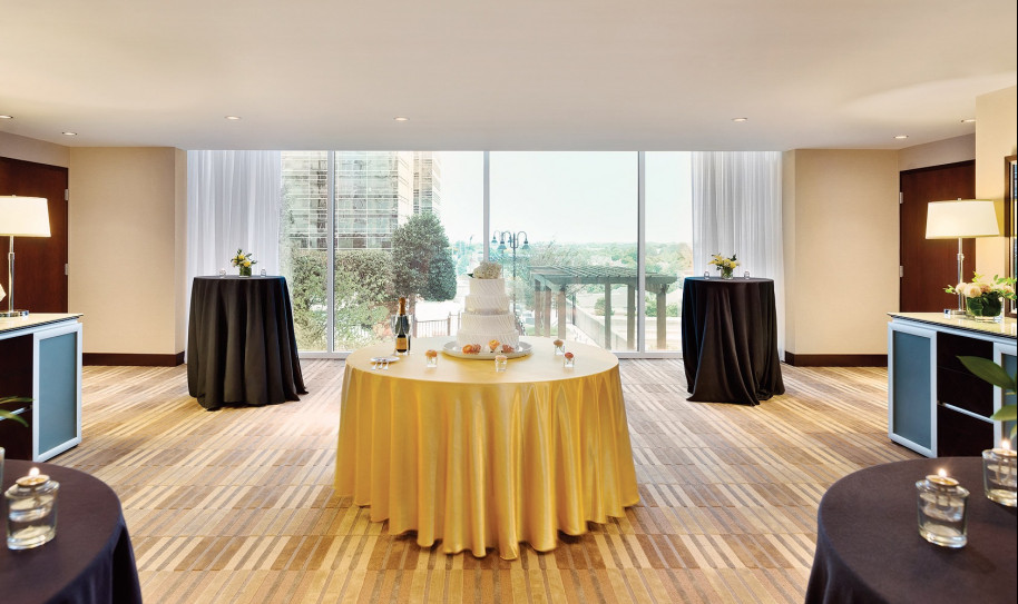 A round table in the center of the room with a cake on it and two taller round cocktail tables in back