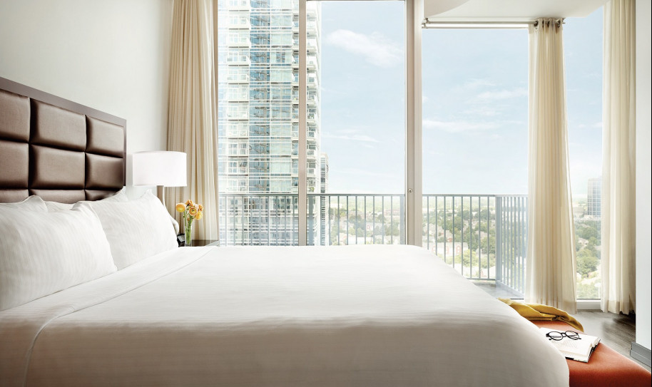 Twelve Downtown Rooms Bed with white sheets and floor length windows facing the city Deluxe 2