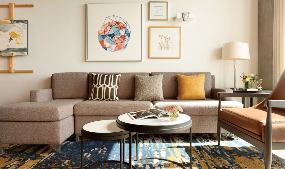 A gray couch with throw pillows, one yellow and one black with white patterns, is in a living room with a circular coffee table, various paintings on the walls, wood floors, a designer carpet, and two hightop chairs angled against a kitchen bar