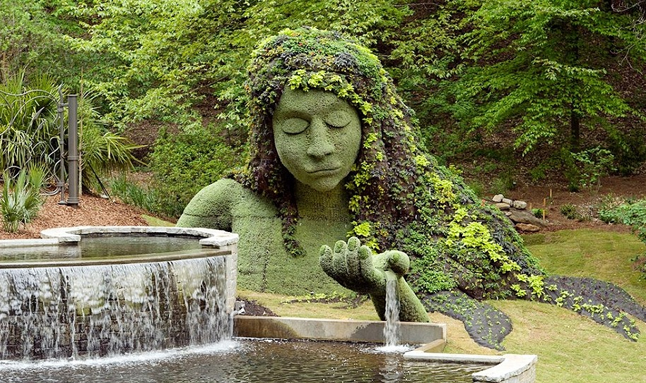 A intricate greenery statue of a woman next to a fountain in Atlanta Botanical gardens