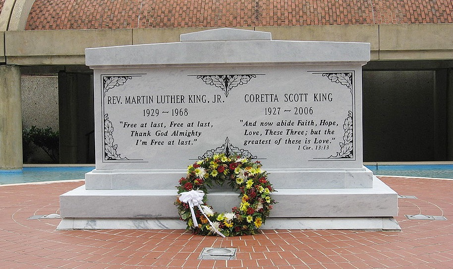 A gravestone with flower wreath in front
