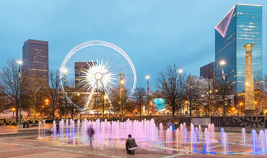 Fountains lit up at night shooting up water at Centennial Olympic Park with ferris wheel in background