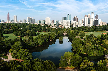 A large park with a pond and many trees sits in front of the Atlanta skyline