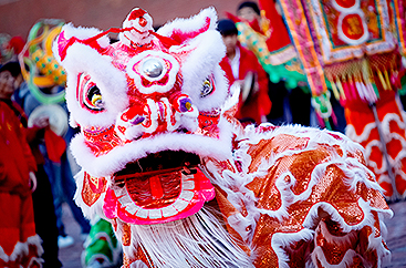 A person dressed in an elaborate dragon costume celebrating Chinese Lunar NewYear