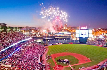 Fireworks shooting off above a crowded baseball stadium