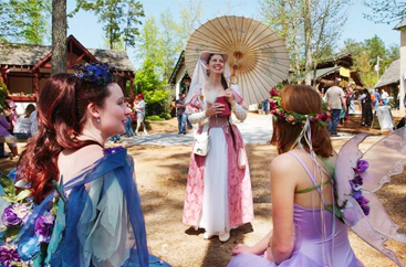 Three women dressed in long dresses with flowers at the Renaissance Festival