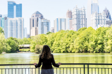 A woman standing next to a railing in front of a pond facing downtown