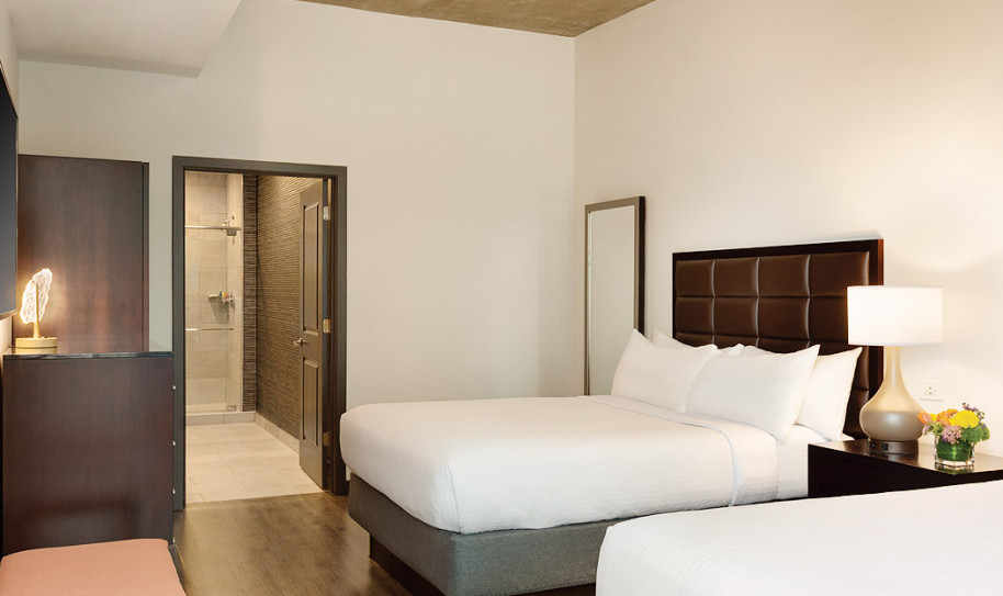 Two beds with white sheets, brown headboard with a view of the bathroom area in distance