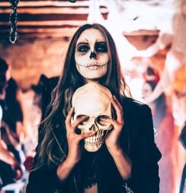 girl with face painted like dia de los muertos holding a skull