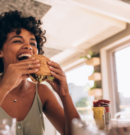 woman laughing while eating burger