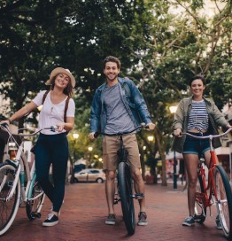 friends smiling and walking with bikes